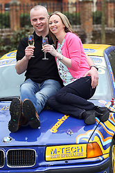 Neil Trotter a  car mechanic and racing driver from Coulsdon, United Kingdom and his partner Nicky Ottaway celebrate on the bonnet of a racing car at a hotel in Dorking, United Kingdom, after winning the £108 million (pounds sterling) EuroMilllions lottery, Tuesday, 18th March 2014. Picture by Stephen Lock / i-Images