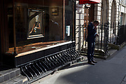 A man stands checking his messages, outside the Rafael Valls Old Master Paintings gallery showing a portrait painting in the window on their Duke Street SW1 premises, on 18th February 2020, in London, England.