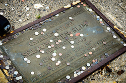 Visitors to Ballarat have left coins on the grave of local prospector Charles Ferge, also known as Seldom Seen Slim.<br /> <br /> Ballarat is a ghost town located in the Panamint Valley near Death Valley National Park. The town was established in 1897. Ballarat served prospectors and miners working in the nearby Panamint mountain range. At its height it had 400-500 residents, but by 1917 the Ballarat was mostly abandoned. In one of the abandoned buildings is graffiti rumored to have been placed there by murderer Charles Manson sometime in the 1960s when Manson and the &ldquo;Manson Family&rdquo; lived at a nearby ranch. Ballarat was also the location for a scene from the movie Easy Rider. Today, only a few buildings remain.