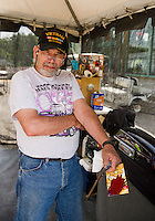 Russ Mowry of Candia gets ready to continue work on a Harley Davidson that he pinstriped in 2008 at his pinstriping tent in front of Thurston's Marine at Weirs Beach Thursday afternoon.    (Karen Bobotas/for the Laconia Daily Sun)