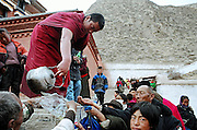 A monk is distributing holy water to the tibetan pilgrims in the monastery of Labrang (Yellow Hats). The water has been used during the ceremony hold in the main Assembly hall and is considered by pilgrims as a  powerfull protection against illness and negative influences. They drink a part of this water and pour the other part on their head. Xiahe, China, March 03, 2007.