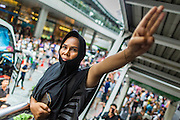 "01 JUNE 2014 - BANGKOK, THAILAND: A woman holds up a three fingered salute during a protest against the Thai military coup at Terminal 21 a popular shopping mall in Bangkok. The salute is from the movie ""The Hunger Games"" and symbolizes it admiration, thanks and good-bye to a loved one. In this case, the loved one is reportedly Thai democracy. The Thai army seized power in a coup that unseated a democratically elected government on May 22. Since then there have been sporadic protests against the coup. The protests Sunday were the largest in several days and seemed to be spontaneous ""flash mobs"" that appeared at shopping centers in Bangkok and then broke up when soldiers arrived. Protest against the coup is illegal and the junta has threatened to arrest anyone who protests the coup. There was a massive security operation in Bangkok Sunday that shut down several shopping areas to prevent the protests but protestors went to malls that had no military presence.    PHOTO BY JACK KURTZ"