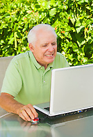 Mature man grimacing and clenching his teeth while working on his laptop computer