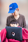 16 MARCH 2012 - SCOTTSDALE, AZ:  MIKE SPEEDIE and his son, JON SPEEDIE, 7, watch movies on Mike's iPad 2 while they wait in line for a New iPad at the Apple Store in Scottsdale. Several hundred people were in line at the Apple Store in the Scottsdale Quarter in Scottsdale, AZ, Friday to buy the New iPad.   PHOTO BY JACK KURTZ