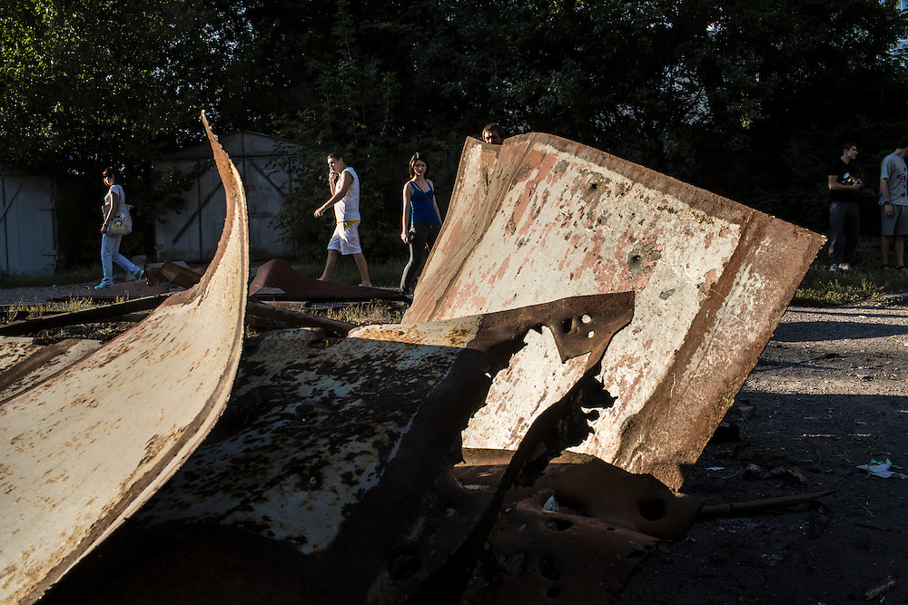 Residents look over the damage to a garage which was destroyed when it and a nearby apartment building were hit by suspected grad rocket strikes on Tuesday, July 29, 2014 in Donetsk, Ukraine.