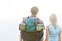 Rear view of young hiking couple standing against clear sky