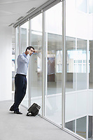 Office worker talking on mobile phone looking out window of empty office space