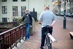 A man on a bicycle is seen talking to a fisherman.<br /> <br /> After living abroad for more than three years I visited my old home town. Wondering what has changed I packed both my curiosity and a camera. (Original posted as part of a photo essay 'Revisiting Familiar Grounds' here: http://www.basslabbers.com/WP/?p=1320)