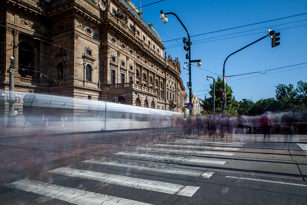 "People passing a street crossing at the National Theater (""Narodni Divadlo"" on the left) in Prague."