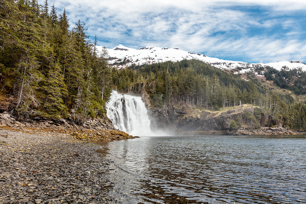 Large waterfall empties into a bay in Prince William Sound in Southcentral Alaska. Spring. Afternoon.