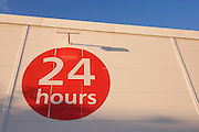 Red circular sign telling shoppers that supermarket is open 24 hours a day and night.