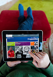 Woman using iPad tablet computer to read The Guardian newspaper App online edition