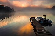 Mountain lake at summer morning covered with fog