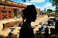 A woman in the courtyard of a typical Solinke household. Global warming and climate change have caused prolonged drought and erratic rains across the Sahel in recent years, exacerbating food insecurity, hunger, poverty and altering traditional ways of life in the region. <br />