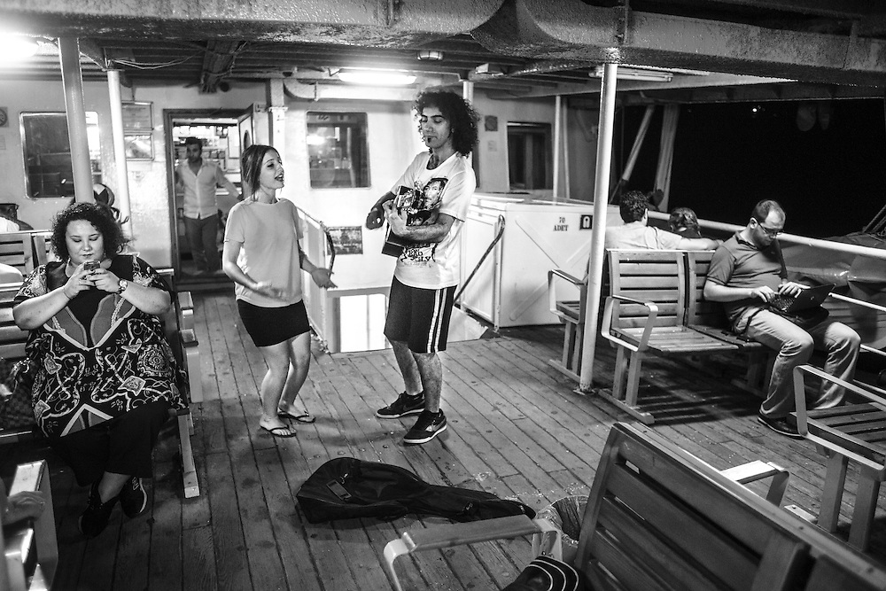 A young couple sings for money inside a Istanbul ferry boat.