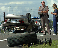 CAPTION: (Holiday: 06/24/2005) The driver's side front wheel torn from a Lincoln before it came to rest on its roof lays along the edge of the road as the Florida Highway Patrol Trooper Stephen Wheeler investigates the four vehicle accident in the northbound lanes of US 19 just south of SR 54 in Holiday Friday (6/24/2005) afternoon.  The crash sent one woman by helicopter to Tampa General Hospital about 3:30 pm.  Her identity and condition were not immediately available Friday..