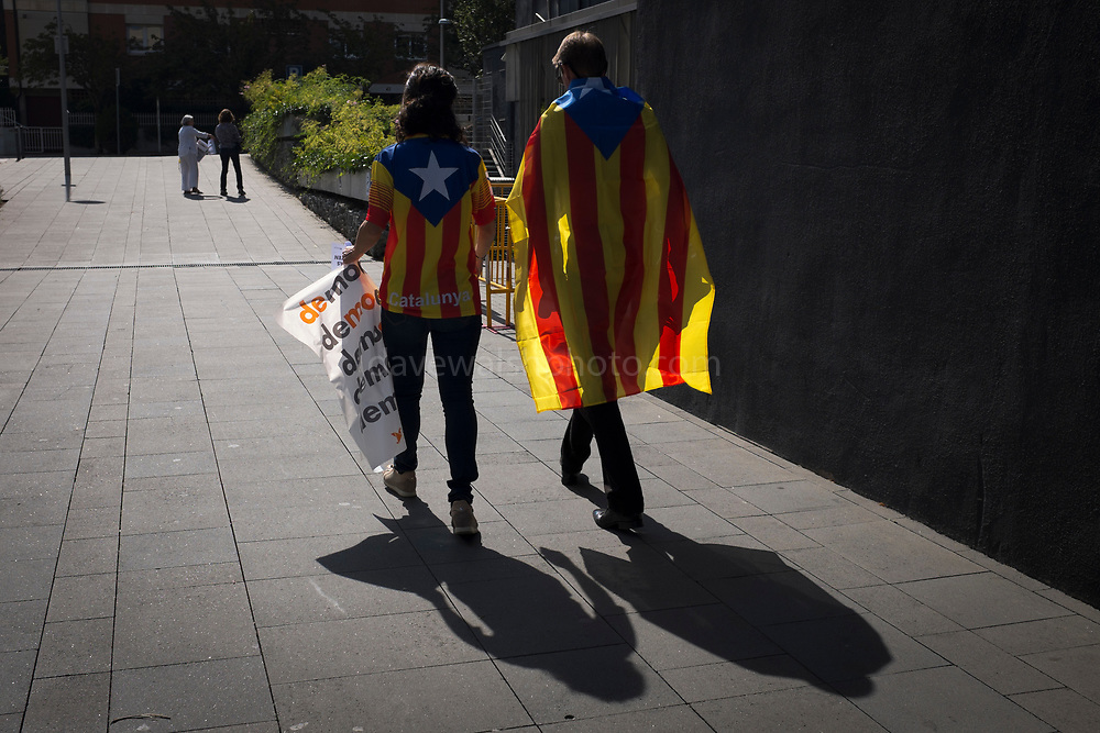 A couple walk home wearing the Estelada, the flag of the Catalan independence movement, after taking part in a large pre-referendum gathering of music and dancing in Sant Cugat del Valles, just outside Barcelona, a week before the planned vote for Catalan independence. The Spanish government has threatened to stop the referendum, having declared it against Spain's constitution.