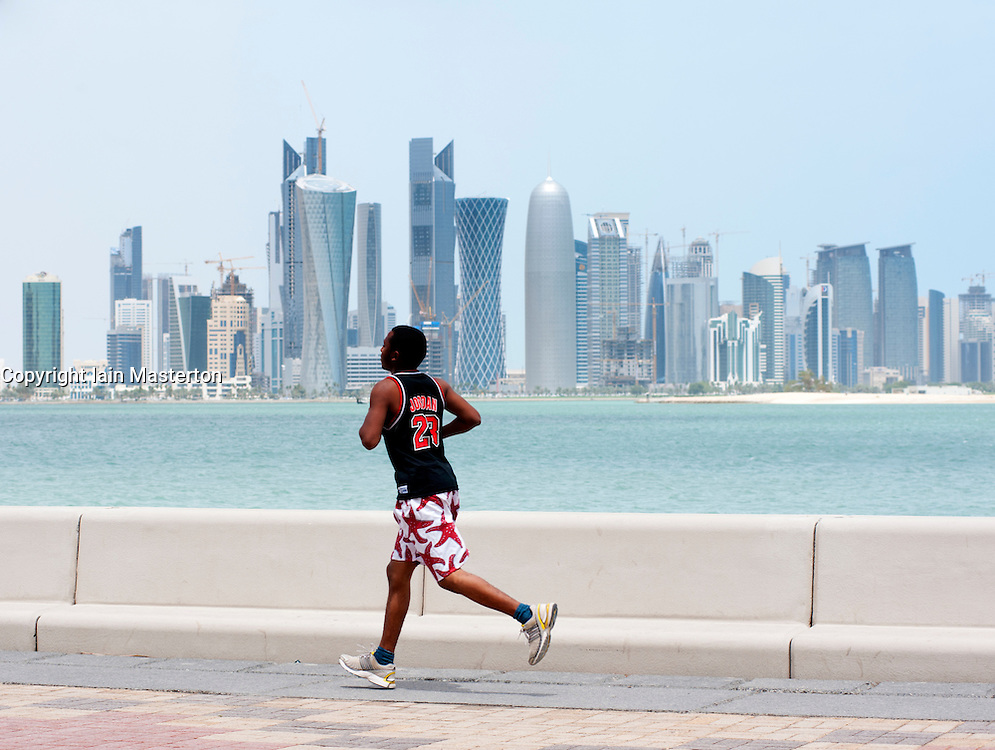 Man running along The Corniche with skyline of Doha Qatar in the distance