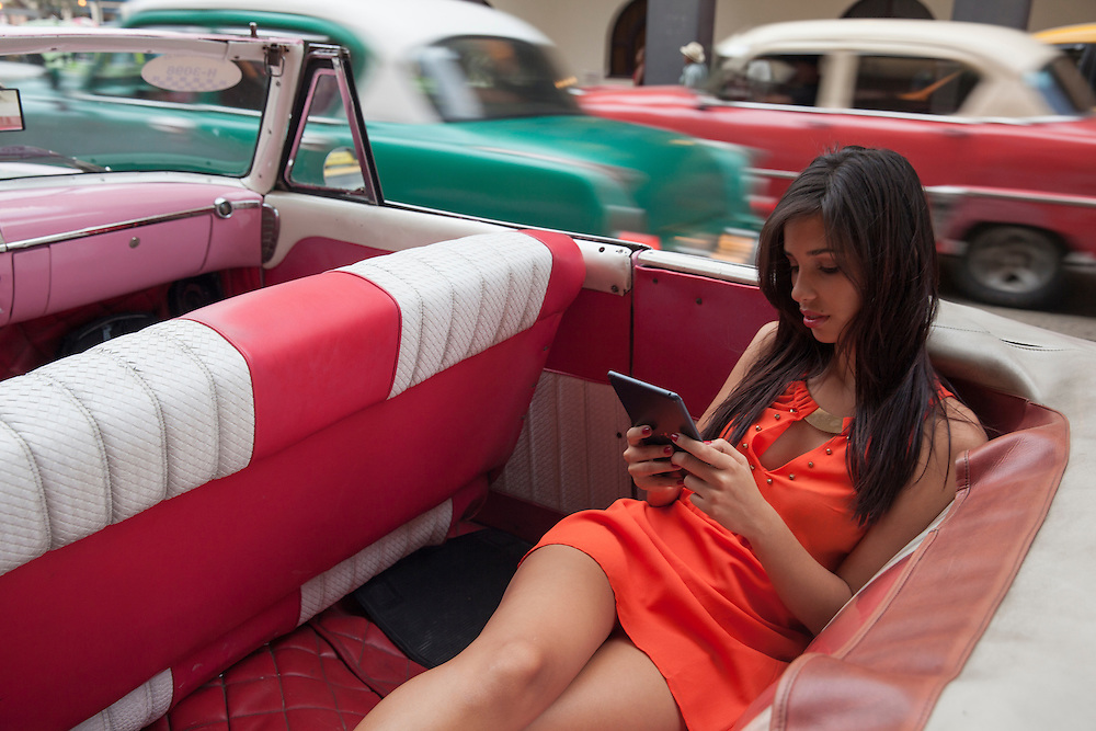 A young woman enjoys reading her tablet while traffic of old cars pass by in the background.