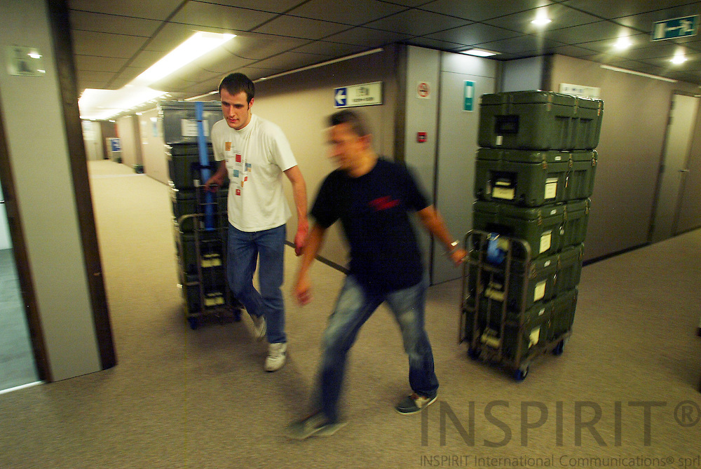 BRUSSELS - BELGIUM - 12 MAY 2006 -- Jean Marie VERLINDEN (R) and his mate collecting moving boxes from the MEP's offices before they are transported to Strasbourg. 732 MEPs have offices in Strasbourg and Brussels. Every month they and their staff move between the 2 cities and uses this kind of boxes for the documents and other stuff. The MEP also calls it the commuting circus. PHOTO: ERIK LUNTANG /