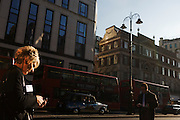 Woman walks along city street in central London.