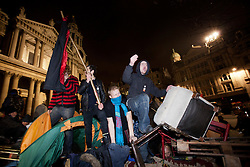 © Licensed to London News Pictures. 28/02/2012. LONDON, UK. Occupy London protesters stands on top of a barricade of pallets and shelving as they attempt to avoid police and bailiffs. After being camped outside St Paul's Cathedral in London for four months anti-capitalist Occupy London demonstrators were tonight evicted by police and bailiffs who moved in shortly after midnight. Photo credit: Matt Cetti-Roberts/LNP