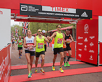 Jenson Button crosses the line #handinhand with Tom Dudden at the Virgin Money London Marathon, Sunday 26th April 2015.<br /> <br /> Scott Heavey for Virgin Money London Marathon<br /> <br /> For more information please contact Penny Dain at pennyd@london-marathon.co.uk