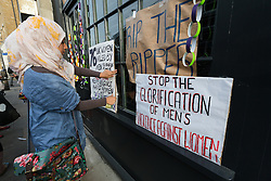© Licensed to London News Pictures. 04/08/2015. London, UK. A woman protestor fixes banners outside the new Jack the Ripper museum at 12 Cable Street, Shadwell, east London. The planning application for the museum stated that the museum would celebrate the historic, current and future contribution of women of the East End of London. The museum had been scheduled to open today, but remains closed.  Photo credit : Vickie Flores/LNP