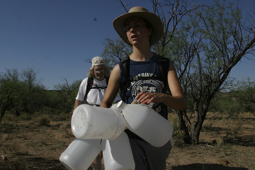 Steve Johnston and another volunteer with the No More Deaths humanitarian organization patrolling the Arizona desert near the town of Arvaka looking for undocumented immigrants in need of help on 13 July 2006. ..Beth Lavely, 24, and Steve, 50, members of the Tucson-based No More Deaths humanitarian organization search the Arizona desert on July 13 2006 for undocumented immigrants lost in the searing desert heat trying to cross the U.S. border. The volunteers provide medical aid and leave water in strategic locations to help immigrants along the mountain roads.