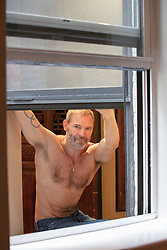 hot man without a shirt looking out a window