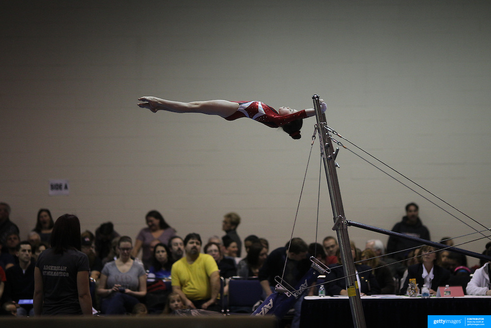 A young gymnasts performs on the uneven bars during competition at the 21st American Invitational 2014 competition at the XL Centre. Hartford, Connecticut, USA. USA. 31st January 2014. Photo Tim Clayton