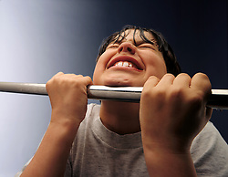 Overweight or obese boy doing pull up with pull up bar