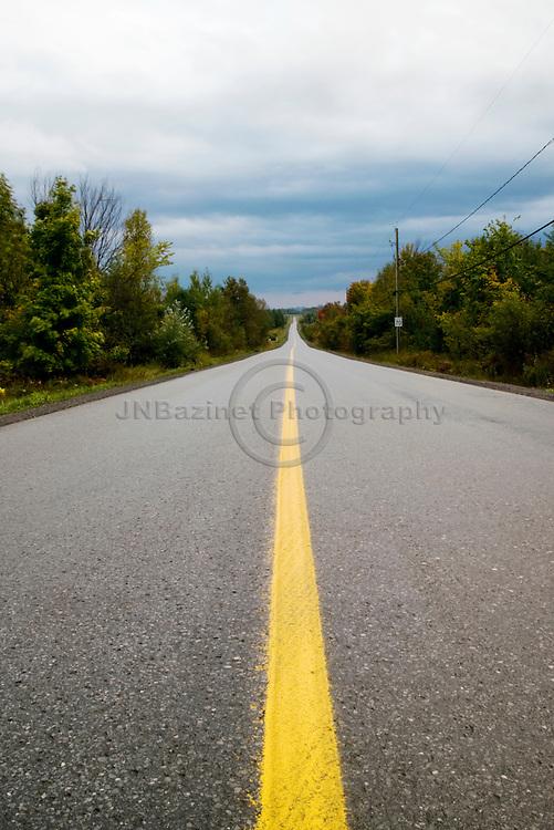 Stormy skies over rural, paved road