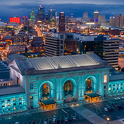Kansas City, Missouri downtown skyline at dusk and Union Station in foreground.