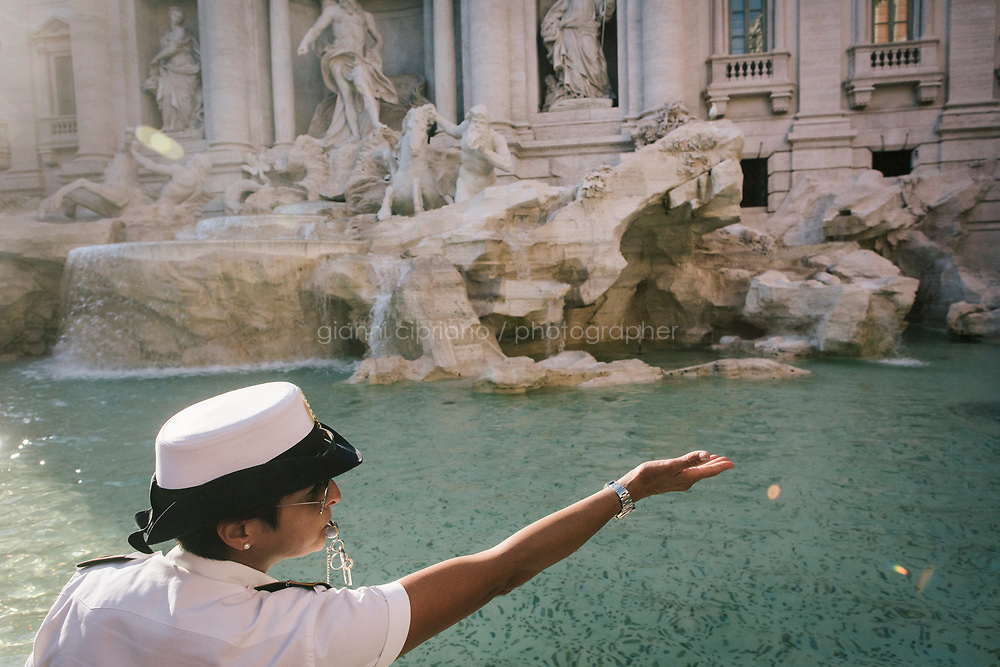ROME, ITALY - 20 JUNE 2017: A Roman policewoman, entrusted to protect the Fountain of Trevi, orders tourists to not sit on the edge of the fountain in Rome, Italy, on June 20th 2017.<br /> <br /> The warm weather has brought a menacing whiff of tourists behaving badly in Rome. On April 12, a man went skinny-dipping in the Trevi fountain resulting in a viral web video and a 500 euro fine.<br /> <br /> Virginia Raggi, the mayor of Rome and a national figurehead of the anti-establishment Five Star Movement,  issued an ordinance involving harsher fines for eating, drinking or sitting on the fountains, for washing animals or clothes in the fountain water or for throwing anything other than coins into the water of the Trevi Fountain, Bernini&rsquo;s Four Fountains and 35 other city fountains of artistic or historic significance around the city.  &ldquo;It is unacceptable that someone use them to go swimming or clean themselves, it&rsquo;s an historic patrimony that we must safeguard,&rdquo; Ms. Raggi said.