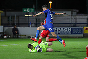 AFC Wimbledon midfielder Callum Reilly (33) hurdling Leyton Orient goalkeeper Sam Sargeant (12) who makes a save during the Leasing.com EFL Trophy match between AFC Wimbledon and Leyton Orient at the Cherry Red Records Stadium, Kingston, England on 8 October 2019.