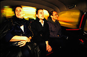 Three people sitting in the back of black cab, London, U.K, 1990s.