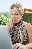 Surprised woman using laptop in back yard