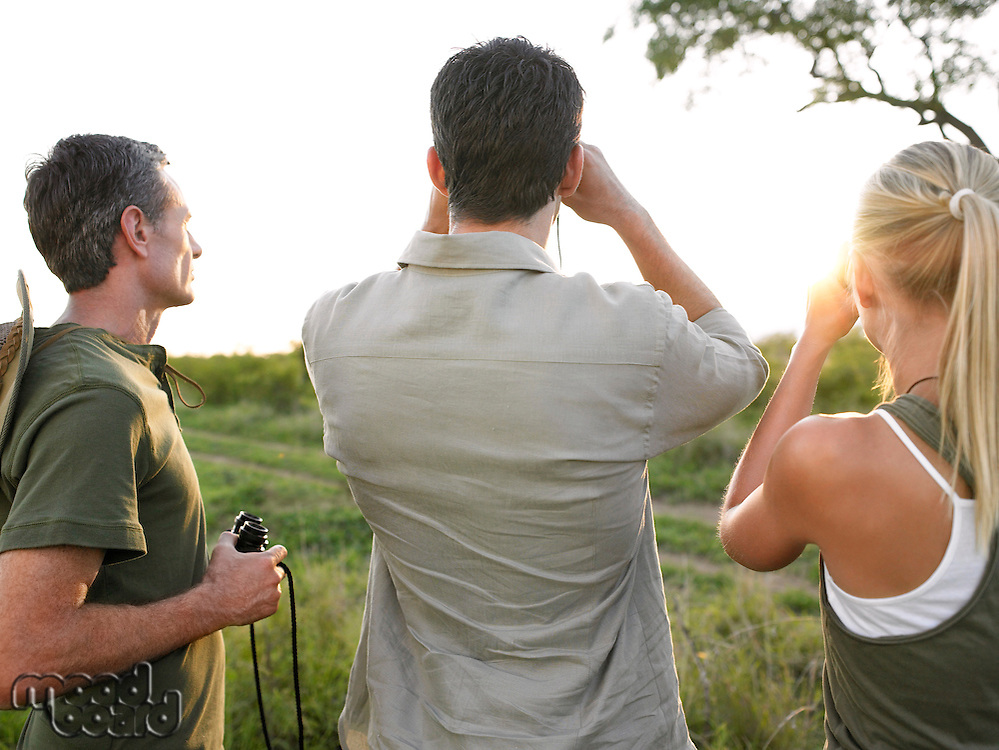 Two men and woman looking through binoculars back view