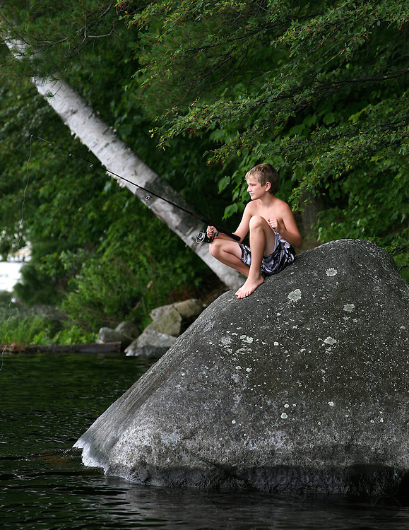 David Cosby sits on a rock to fish on Tupper Lake near the town of Tupper Lake, New York in Adirondack Park..  Photo by Gary Cosby Jr.