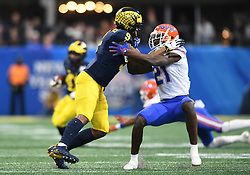 Florida Gators defensive back Trey Dean III (21) gets blocked by Michigan Wolverines defensive back Gemon Green (9) during the Chick-fil-A Bowl Game at  the Mercedes-Benz Stadium, Saturday, December 29, 2018, in Atlanta. ( AJ Reynolds via Abell Images for Chick-fil-A Kickoff)