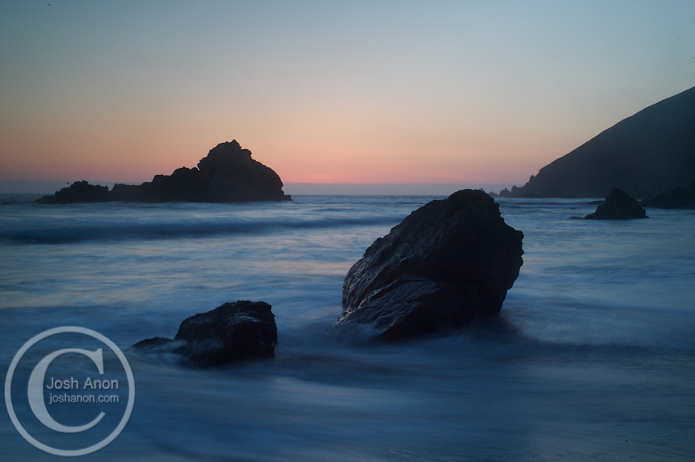 Waves break along rocks in Big Sur, California at sunset.
