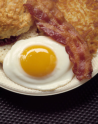 close-up one fried egg sunny side up biscuit bacon hash brown home fry potato white plate potatoes hearty breakfast Bon Appetit