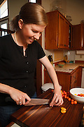 USA, Oregon, Eugene, young woman slicing tomatoes for bruschetta in her kitchen. MR