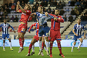 Jason Pearce (Wigan) has his shirt pulled while jumping to head the ball from a corner during the Sky Bet League 1 match between Wigan Athletic and Gillingham at the DW Stadium, Wigan, England on 7 January 2016. Photo by Mark P Doherty.