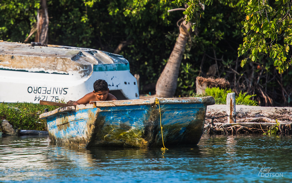 A young Belizian boy looks to make one of the crafts seaworthy.