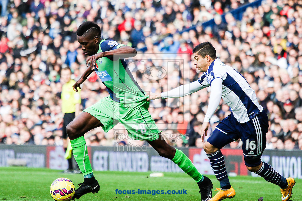 Sammy Ameobi of Newcastle United (left) is held back by Cristian Gamboa of West Bromwich Albion (right) during the Barclays Premier League match at The Hawthorns, West Bromwich<br /> Picture by Andy Kearns/Focus Images Ltd 0781 864 4264<br /> 09/11/2014