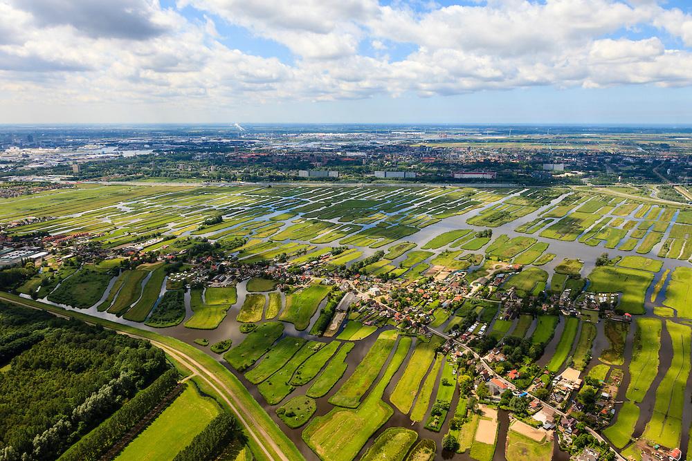 Nederland, Noord-Holland, Gemeente Oostzaan, 14-06-2012; polder Oostzaan, en in de voorgrond het lintdorp Oostzaan. Zaandam en autosnelweg A9 ophef tweede plan. De verkaveling in het gebied is het resultaat van veenontginning. .Polder and village Oostzaan, north of Amsterdam (at the horizon). The division in plots in the area is the result of peat extraction..luchtfoto (toeslag), aerial photo (additional fee required);.copyright foto/photo Siebe Swart