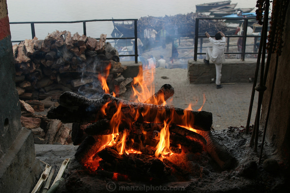 "The ""eternal fire"" at the cremation grounds at Manikarnika Ghat. All funeral pyres are lighted from embers from this fire which burns above the ghat. One hundred or more times a day male family members carry a loved one's body through the narrow streets on a bamboo litter to the Ganges River shore,  place of pilgrimage for Hindus during life, and at death."