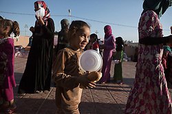 Licensed to London News Pictures. 22/10/2016. A young Iraqi IDP, newly arrived from areas where the Mosul Offensive is taking place, smiles after receiving bread from an aid worker in a school at the Dibaga refugee camp near Makhmur, Iraq. Upon arriving at the camp women and children stay in the school for around 10 - 15 days whilst completing the registration process.<br />